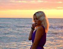 在海的体贴的白肤金发的女孩日落的 图库摄影