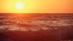 在海的大波浪靠岸在日落 慢动作录影美丽的波浪在橙色太阳的背景的 影视素材