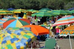 在海的岸堆的伞拥挤海滩的 免版税库存图片