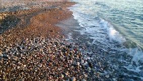 在海的岸的一个小小卵石和美好的逃亡挥动 库存图片