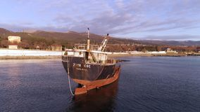 在海的岸的老被放弃的小船有海岸线和山的在背景 射击 被击毁的,下沉的船  影视素材