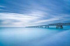 在海的工业码头。侧视图。长的曝光摄影。 免版税库存照片