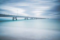 在海的工业码头。侧视图。长的曝光摄影。 库存照片
