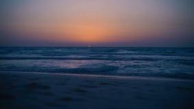 在海的惊人的神秘的血淋淋的日落 清楚的天空 有小波浪的风平浪静 起波纹在沙子的波浪 看法从 影视素材