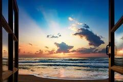 在海的日出,富有的光的反射视图通过窗口 库存照片