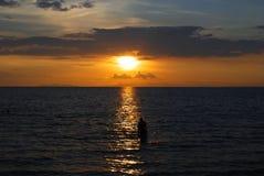 在海的日落有人的 库存照片