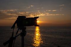 在海的日落有在照相机后的太阳的在三脚架 免版税库存照片