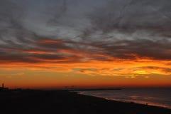 在海的日落有橙色天空和剧烈的云彩的 免版税库存图片