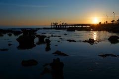 在海的日落有石头和渔夫的 免版税库存图片