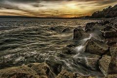 在海的日落有飞溅的在岩石挥动 免版税库存照片