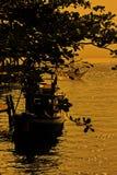 在海的日落灿烂光辉以后,有一个渔船的剪影的 库存图片