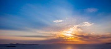 在海的明亮的五颜六色的日落有美丽的云彩的 免版税库存照片