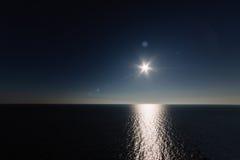 在海的朝阳有一条轻的道路的 库存照片