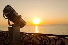 在海的海岸的双筒望远镜 在日落背景的旅游望远镜在江边的 夏天 免版税库存照片