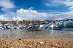 在海的渔船在米科诺斯岛,希腊靠岸 多云天空的海村庄 山风景的白色房子与好 库存图片