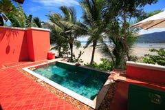 在海的游泳池海湾的,在庭院旁边的太阳懒人和大厦 库存图片