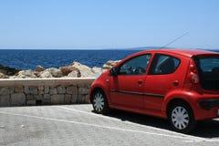 在海的红色汽车 免版税库存照片