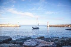 在海的美丽的白色游艇,在lightho的背景中 免版税库存图片