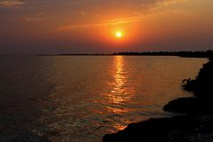 在海的美好的日出有在水和海滨剪影的金黄反射的在天际 夏天海背景 假期Conce 免版税库存图片