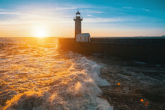 在海的美好的日落一座石码头和灯塔 库存图片