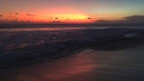 在海的美好的cloudscape有波浪的和在日落,巴厘岛,印度尼西亚,4k英尺长度录影期间的人剪影 股票录像