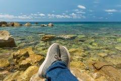 在海的背景的腿 免版税库存照片