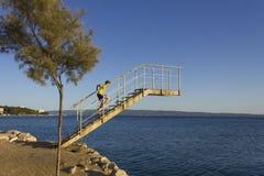 在海的跳台在克罗地亚,有对此的一个孩子的 免版税库存照片