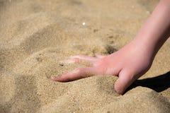 在海的软的沙子的手 免版税库存图片