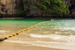 在海的风景看法有黄色浮体的和从Phra Nang的一个岩石靠岸 免版税图库摄影