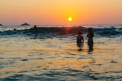 在海的风景美好的浪漫日落有在站立的人剪影的在水中和享用晚上橙色太阳在亚当 图库摄影