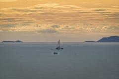 在海的风船航行日落时间的 库存图片