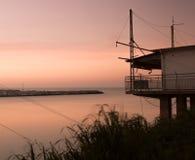 在海的高跷房子在日落前面 库存照片