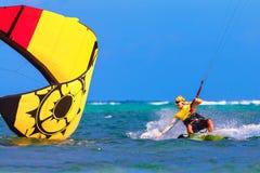 在海背景极端体育Kitesur的年轻smiing的kitesurfer 免版税库存照片