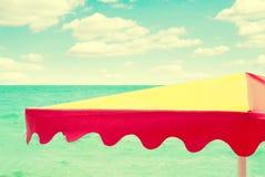 在海背景的沙滩伞,葡萄酒减速火箭的样式 免版税库存照片