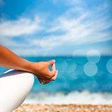 在海背景的瑜伽手 库存图片