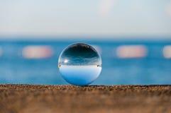 在海背景的玻璃透明球和 免版税库存图片