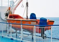 在海船的甲板的橙色救生艇 库存照片