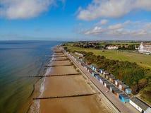 在海艾塞克斯鼠蹊海边水海蓝色云彩海滩小屋草景色的海滩frinton挥动步树 免版税库存照片