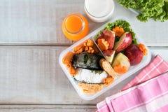 在海草包裹的午餐盒、米用香肠,鸡蛋和苹果 免版税库存照片