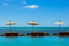 在海视图的三张海滩睡椅在蓝天 库存照片