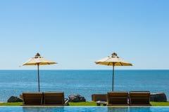 在海视图的两张海滩睡椅在蓝天 免版税库存图片