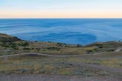 在海角Meganom的风平浪静风景在日落 克里米亚的半岛的东海岸 免版税库存图片