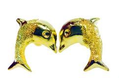 在海豚形状的金下垂有浮雕的贝壳耳环首饰被隔绝的  免版税库存照片
