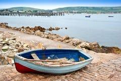 在海边城镇生成滑动式造船架的老划艇  库存照片