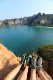在海边山岩石的攀岩运动员腿 免版税库存照片