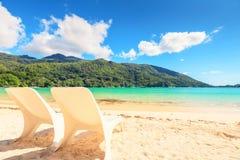 在海边岸的两张白色海滩睡椅 免版税库存图片