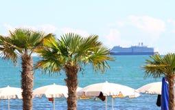 在海边旅游村庄和游轮的棕榈 免版税图库摄影