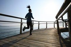 在海边木板走道的运动的女性慢跑者早晨锻炼 免版税库存照片