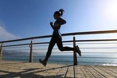 在海边木板走道的运动的女性慢跑者早晨锻炼 免版税库存图片