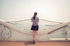 在海边栏杆的亚洲女孩后面 免版税库存图片